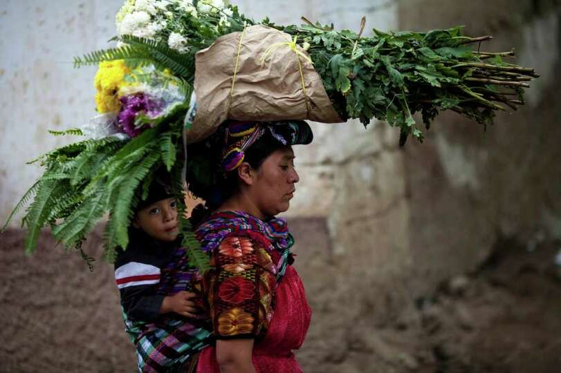A child rides piggy-back as his mother carries bouquets of flowers to the local cemetery to decorate