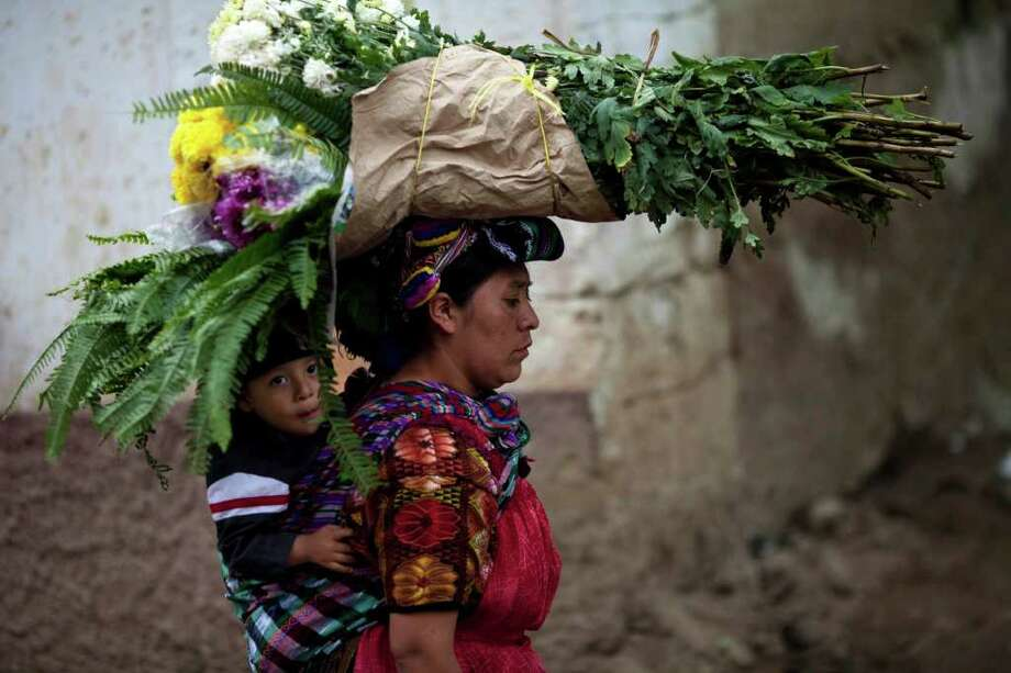 A child rides piggy-back as his mother carries bouquets of flowers to the local cemetery to decorate the graves of relatives during the Day of the Dead celebrations in Zunil, Guatemala, Tuesday Nov. 1, 2011. Photo: AP