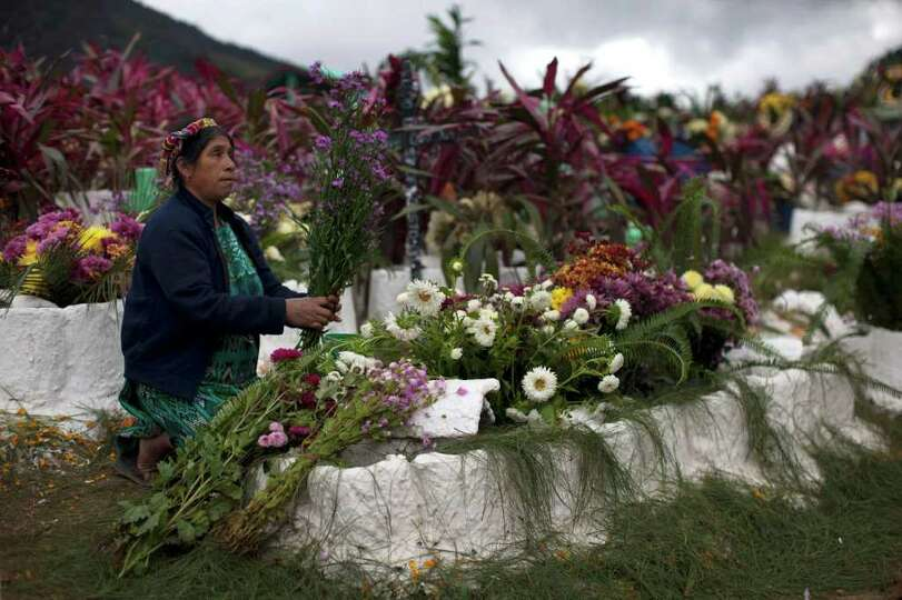 A woman arranges a bouquet of flowers while decorating the graves of relatives during the Day of the