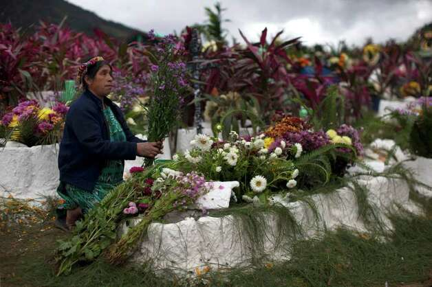 A woman arranges a bouquet of flowers while decorating the graves of relatives during the Day of the Dead celebrations in Zunil, Guatemala, Tuesday Nov. 1, 2011. A tradition that coincides with All Saints Day and All Souls Day on Nov. 1 and 2., the ritual of dressing the graves with flowers is common throughout Latin America as is having a picnic at the departed relative's gravesite. Photo: AP