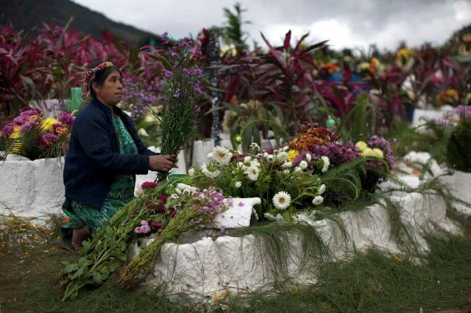 A woman arranges a bouquet of flowers while decorating the graves of relatives during the Day of the Dead celebrations in Zunil, Guatemala, Tuesday Nov. 1, 2011.  Photo: AP
