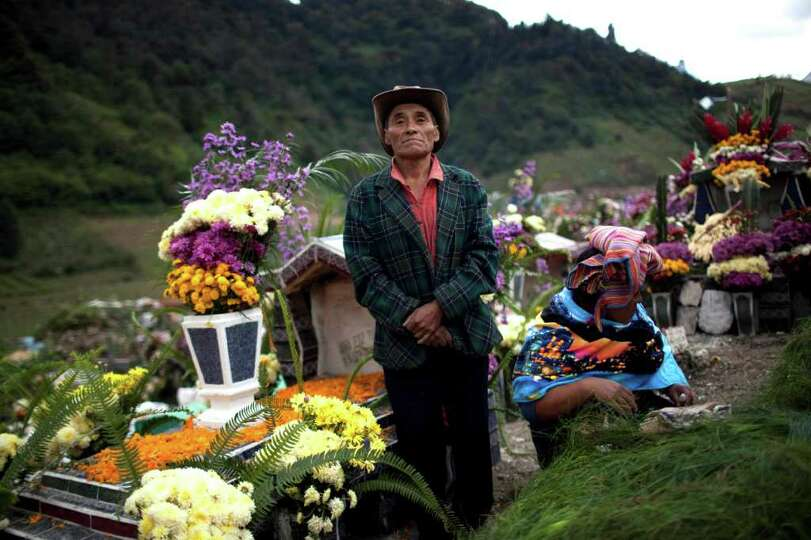 A man stands next his wife as she decorates a relative's grave during the Day of the Dead celebratio