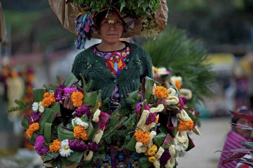 A woman carries a bundle of flowers on her head and two wreaths to decorate the graves of relatives,