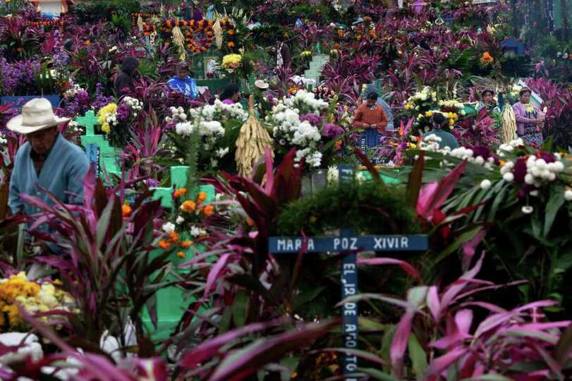 Family members decorate the graves of a departed relatives, in Zunil, Guatemala, Tuesday Nov. 1, 201