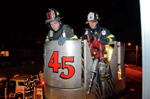 Ty Middleton (left) and Lt. Matt Gladstone are perched high above Dorlen Road in a bucket, lining up to an attic window, as the Belltown Fire Department practices search-and-rescue training drills at their firehouse in Stamford, CT on Tuesday evening November 1, 2011. Colleagues are below near the fire truck. Photo: Shelley Cryan / Shelley Cryan freelance; Stamford Advocate freelance