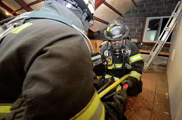 Zack Lamotta and Alex Sanabria (facing camera) simulate a rescue in an attic training area as the Belltown Fire Department practices search-and-rescue training drills at their firehouse on Dorlen Road in Stamford, CT on Tuesday evening November 1, 2011. Photo: Shelley Cryan / Shelley Cryan freelance; Stamford Advocate freelance