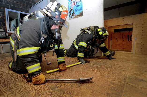 Zack Lamotta (foreground) and Alex Sanabria search an attic training area as the Belltown Fire Department practices search-and-rescue training drills at their firehouse on Dorlen Road in Stamford, CT on Tuesday evening November 1, 2011. Photo: Shelley Cryan / Shelley Cryan freelance; Stamford Advocate freelance