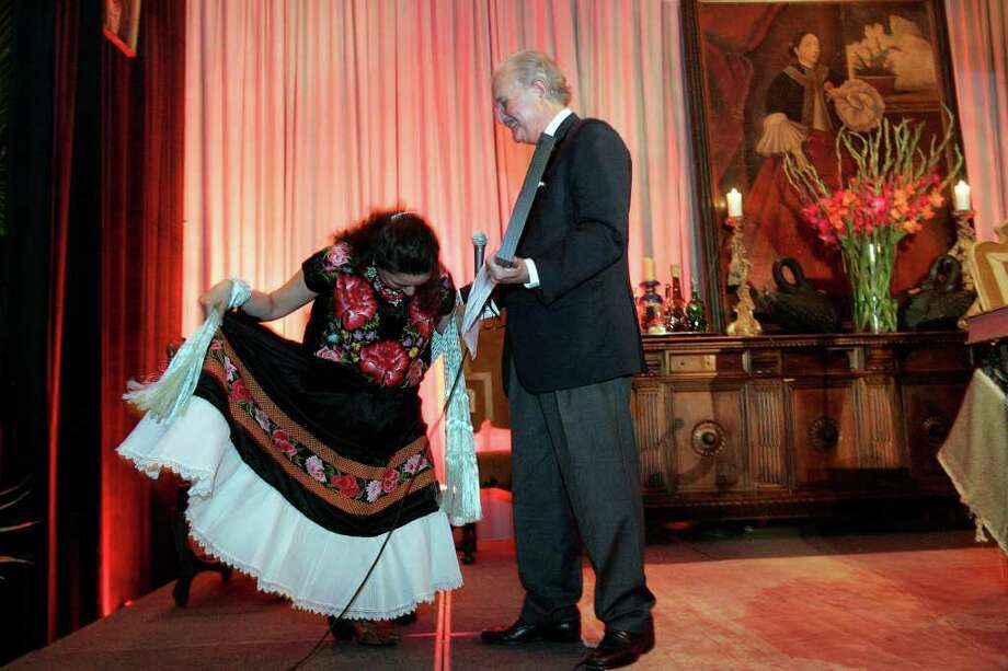 Sandra Cisneros (left) bows to Carlos Fuentes as she gives him an award from the San Antonio Public Library Foundation on Oct. 21, 2005. Photo: Toby Jorrin, For The Express-News / SAN ANTONIO EXPRESS-NEWS