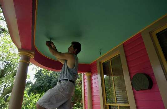 Bill Sanchez installs a porch swing at the lower King William home of author Sandra Cisneros. The house was painted a purple color that created some local controversy in that historic area, but recently they went through a city review process and changed the color to an intense pink color. JOHN DAVENPORT / STAFF Photo: JOHN DAVENPORT, SAN ANTONIO EXPRESS-NEWS / SAN ANTONIO EXPRESS-NEWS