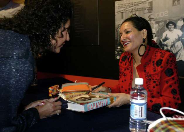 Author Sandra Cisneros (left) talks with a fan while signing books after a book reading at the Mexican Fine Arts Center Museum in Chicago, Ill. Thursday, October 3, 2002.  (Photo by Peter Thompson/Special to the Express-News) Photo: PETER THOMPSON, SAN ANTONIO EXPRESS NEWS / SAN ANTONIO EXPRESS NEWS