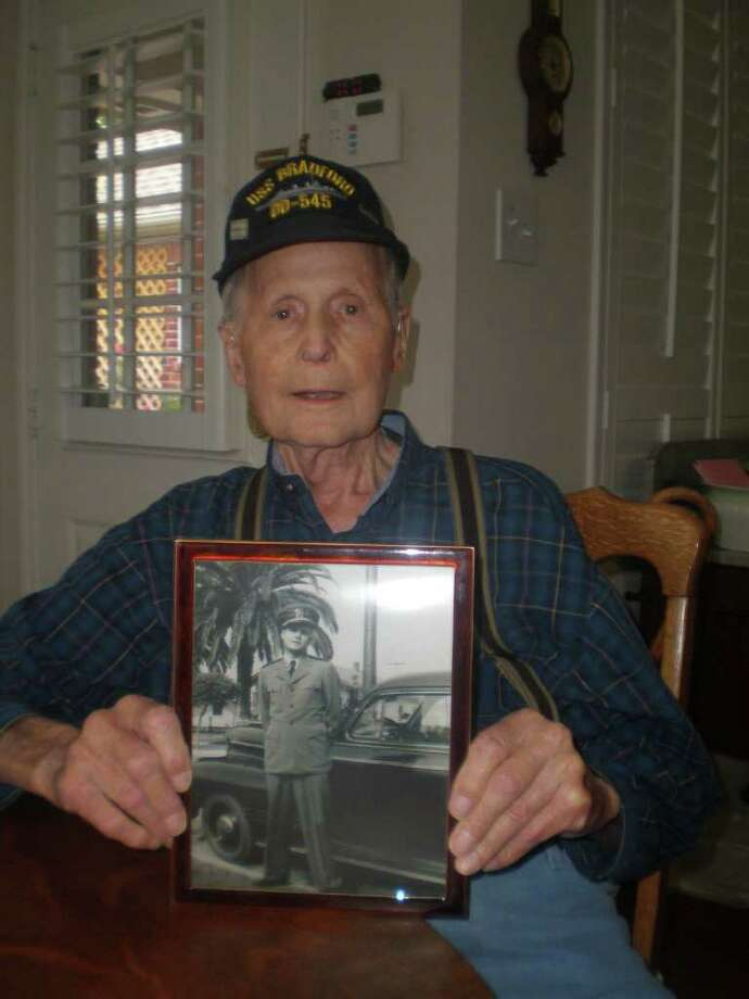 Photo: Courtesy of Denise Moore-Null: Jim Richburg, holds a photograph of himself not long after being commissioned an Ensign in the US Navy. Ensign Richburg was one of a few remaining surviving sailors who attended a reunionn for the USS Bradford  in San Diego earlier this year. Photo: Denise Moore-Null