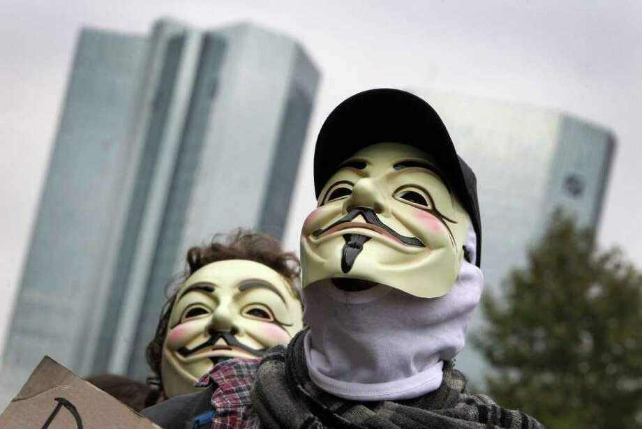 """Demonstrators wearing V-masks walk past the headquarters of Deutsche Bank as they take part in a protest march as part of the """"Occupy Frankfurt"""" movement in Frankfurt am Main, on October 29, 2011 to protest against the financial system. Inspired by the US Occupy Wall Street movement and Spain's """"Indignants"""", the """"Occupy Frankfurt"""" protesters have erected in October around 50 tents in the city-centre park next to the ECB's Eurotower headquarters. The V-mask, which is also known as Guy Fawkes mask and which first appeared in the """"V for Vendetta"""" movie from the year 2006, has become a symbol for the Anonymous group and the Occupy Wall Street movement.      AFP PHOTO / DANIEL ROLAND (Photo credit should read DANIEL ROLAND/AFP/Getty Images) Photo: DANIEL ROLAND / AFP"""