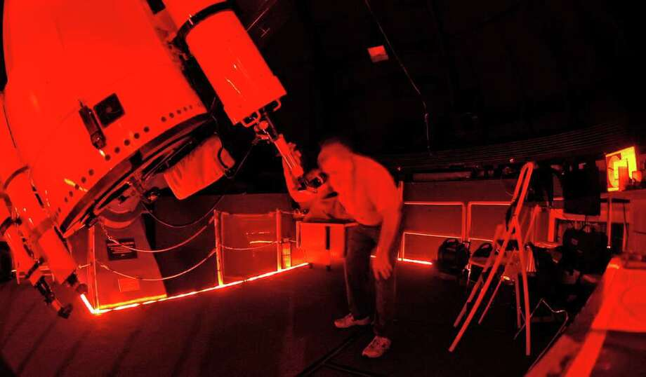 Before trying to take photographs of Jupiter, Bill Christian adjusts the position of the 36 inch wide Gueymard Research Telescope to put the planet in the center of his eyepiece. When the sky darkens and the stars begin to shine, all white lights are put out and only low levels of red light are allowed, otherwise night vision, which is needed, is lost.  Dave Ryan/The Enterprise