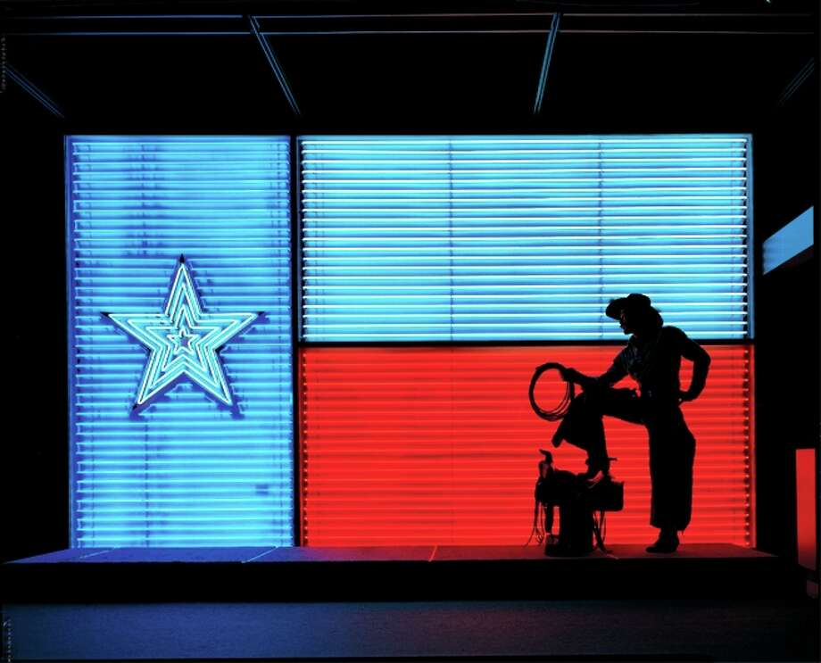 Iconic Texas photographs like this cowboy silhouetted in front of the neon Texas flag at the Insitute of Texan Cultures are Griff Smith's specialty, which were on display until March of 2012. Photo: Courtesy Griff Smith