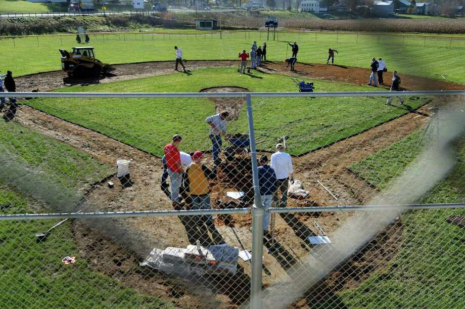ValleyCats front office staff join volunteers as they revamp a baseball field on Wednesday, Nov. 2, 2011, at Schoharie Little League in Schoharie, N.Y. The field was damaged by flooding from Tropical Storm Irene. The group rebuilt the pitchers mound and home plate, cut baselines, laid down infield sod and placed new clay on infield surfaces. (Cindy Schultz / Times Union) Photo: Cindy Schultz / 00015217A