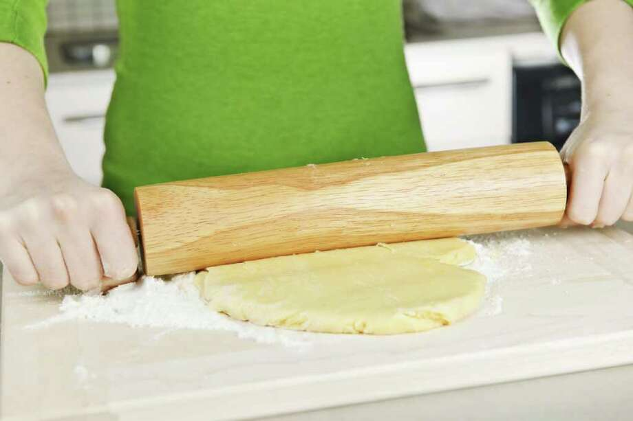 Spreading out cookie dough with wooden rolling pin Photo: Elena Elisseeva / Elenathewise - Fotolia