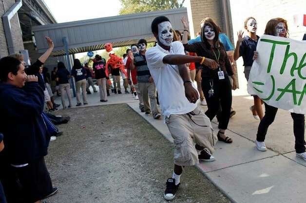 Theater Arts student James Williams, 15, dances to the music made by the marching band as he walks with his fellow Theater Arts students and their teacher, Lauren Morales-Davenport (right) during the Dia de los Muertos parade at Nimitz Middle School in San Antonio on Nov. 2, 2011. Photo: LISA KRANTZ, SAN ANTONIO EXPRESS-NEWS / SAN ANTONIO EXPRESS-NEWS