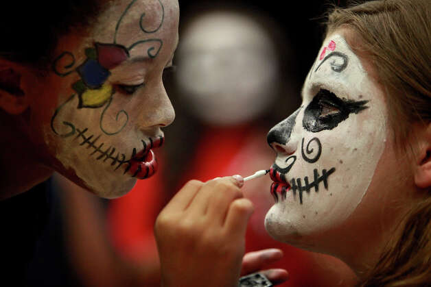 Eve Younger, 13, left, paints the face of Scarlett Mar, 13, as they get ready with fellow Theater Arts students for the Dia de los Muertos parade at Nimitz Middle School in San Antonio on Nov. 2, 2011. Photo: LISA KRANTZ, SAN ANTONIO EXPRESS-NEWS / SAN ANTONIO EXPRESS-NEWS