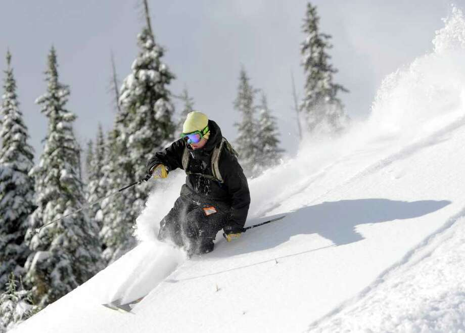 In this photo provided by Colorado Ski Country USA, a skier makes a turn in some fresh powder during the opening of ski season at Wolf Creek Ski Area in Pagosa Springs, Colo., Saturday, Oct. 8, 2011. With a 36 inch base, Wolf Creek is the first resort to turn it's lifts this season. (AP Photo/Colorado Ski Country USA, Jack Dempsey) Photo: Jack Dempsey / Colorado Ski Country USA
