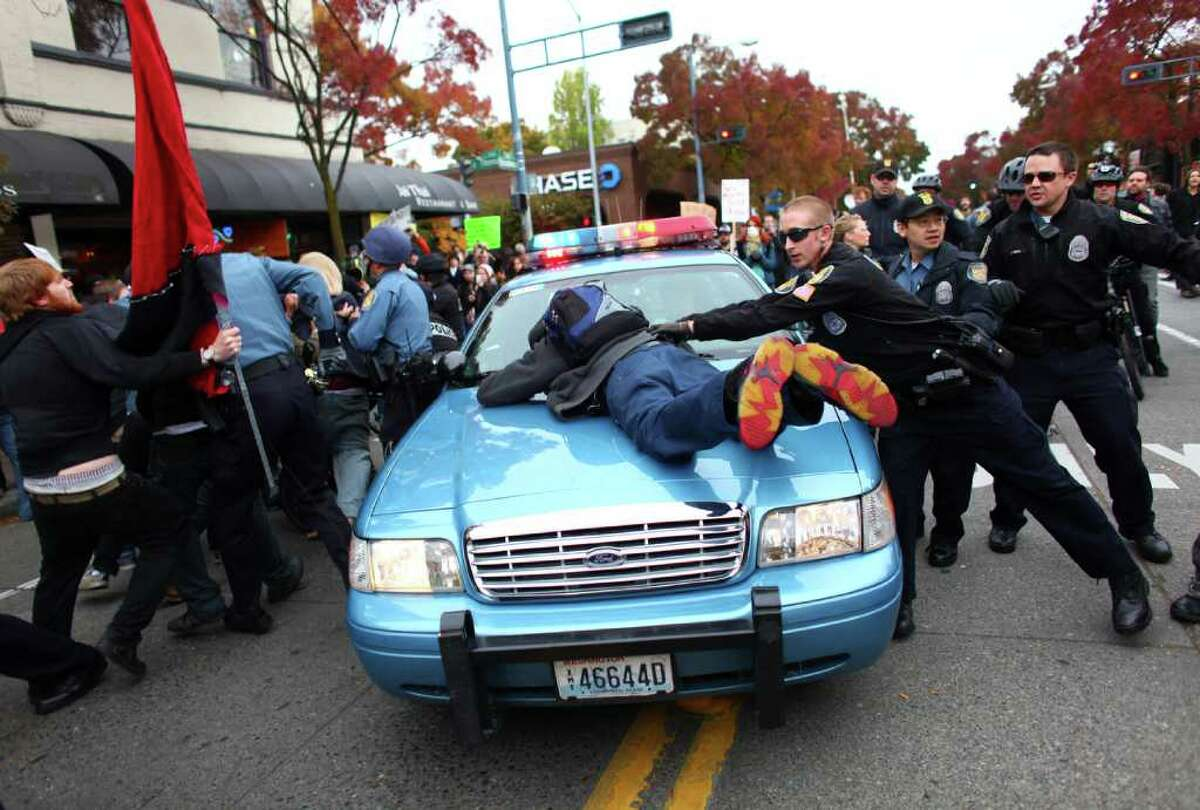 A man jumps onto the hood of a police cruiser as officers try to remove an arrested protester during an Occupy Seattle protest outside a Chase Bank branch on Broadway Avenue East and East Thomas Street on Wednesday, Nov. 2, 2011. Protesters connected themselves together with pipes inside the branch. When they were removed from the bank, a mini-riot ensued as police worked to keep back protesters. JPMorgan Chase CEO Jamie Dimon later spoke at an event in downtown Seattle.