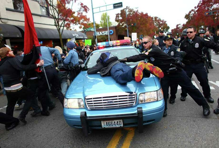 A man jumps onto the hood of a police cruiser as officers try to remove an arrested protester during an Occupy Seattle protest outside a Chase Bank branch on Broadway Avenue East and East Thomas Street on Wednesday, Nov. 2, 2011. Protesters connected themselves together with pipes inside the branch. When they were removed from the bank, a mini-riot ensued as police worked to keep back protesters. JPMorgan Chase CEO Jamie Dimon later spoke at an event in downtown Seattle. Photo: JOSHUA TRUJILLO / SEATTLEPI.COM