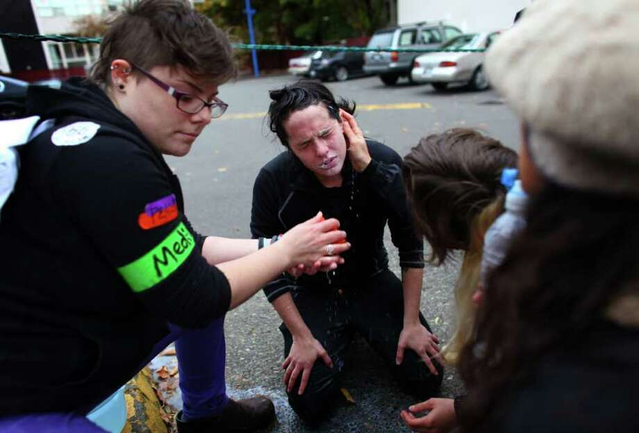 A woman is treated after being maced in the face during an Occupy Seattle protest outside a Chase Bank branch on Capitol Hill on Wednesday, Nov. 2, 2011. Photo: JOSHUA TRUJILLO / SEATTLEPI.COM