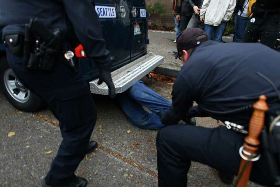 A man holds onto the underside of a paddy wagon as it tries to drive away as police remove protesters arrested during an Occupy Seattle protest outside a Chase Bank branch on Capitol Hill on Wednesday, Nov. 2, 2011. Photo: JOSHUA TRUJILLO / SEATTLEPI.COM