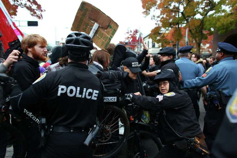 Police and protesters shove each other during an Occupy Seattle protest outside a Chase Bank branch on Capitol Hill on Wednesday, Nov. 2, 2011. Photo: JOSHUA TRUJILLO / SEATTLEPI.COM