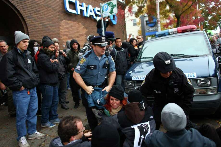 Police try to remove protesters from in front of a police vehicle during an Occupy Seattle protest outside a Chase Bank branch on Capitol Hill on Wednesday, Nov. 2, 2011. Photo: JOSHUA TRUJILLO / SEATTLEPI.COM