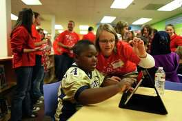 Jessica Siemens helps a student with a new iPad during the unveiling of a new library at West Seattle Elementary School on Wednesday, November 2, 2011. The school was one of 42 across the country that were chosen by Target's School Library Makeover Program. The new library includes 2,000 new books, new computers 10 iPads, furniture paint and more.
