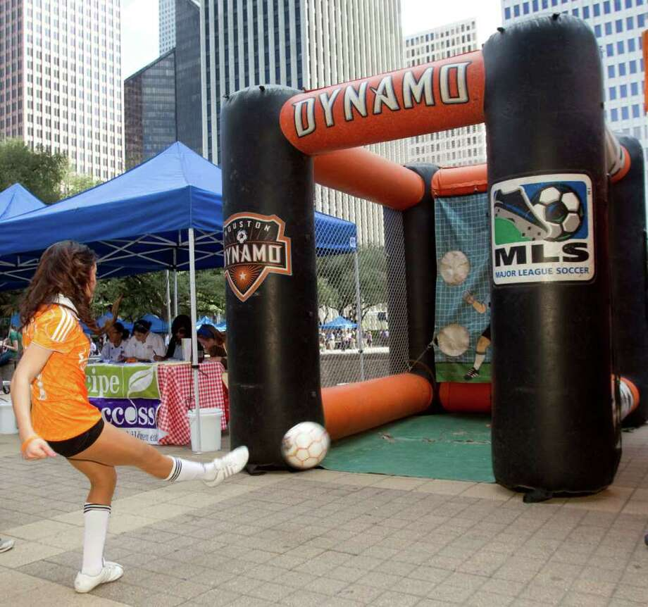 Houston Dynamo cheerleader Andreina kicks a soccer ball during a playoff rally for the MLS team in front of City Hall Wednesday, Nov. 2, 2011, in Houston. Mayor Annise Parker urged Houstonians to cheer on the Dynamo in its playoff match Thursday against the Philadelphia Union. Photo: Brett Coomer, Houston Chronicle / © 2011 Houston Chronicle