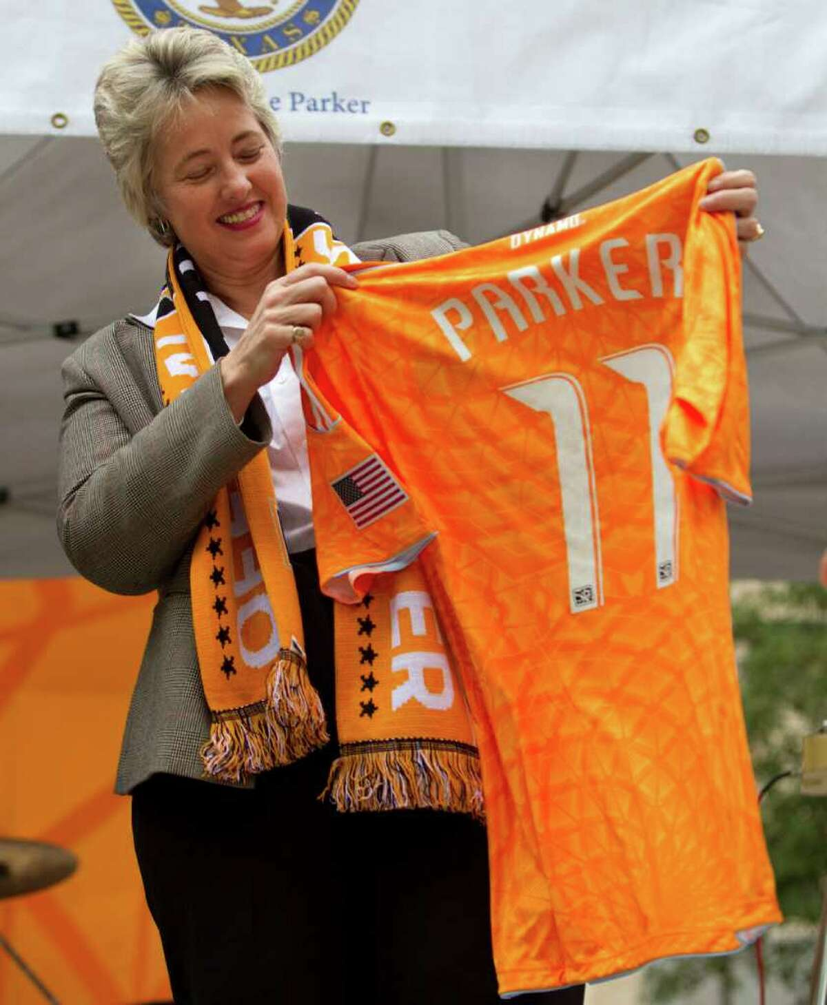 Mayor Annise Paker holds up a Houston Dynamo jersey during a playoff rally for the soccer team on the front steps of City Hall Wednesday, Nov. 2, 2011, in Houston. The mayor urged Houstonians to cheer on the Dynamo in its MLS playoff match Thursday against the Philadelphia Union.
