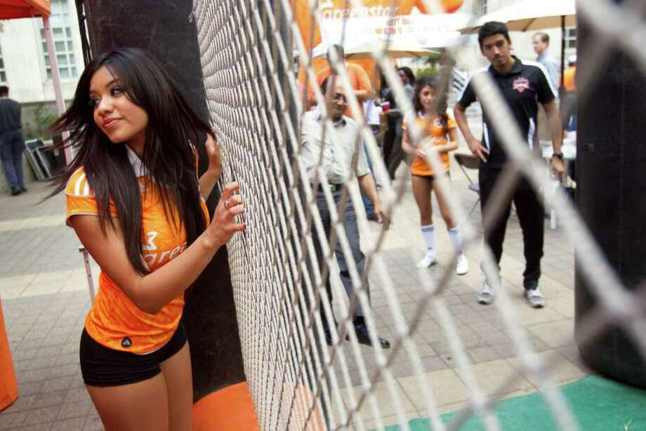 Houston Dynamo cheerleader Esmeralda stands outside a net as people kick soccer balls during a playoff rally for the MLS team in front of City Hall Wednesday, Nov. 2, 2011, in Houston. Photo: Brett Coomer, Houston Chronicle / © 2011 Houston Chronicle