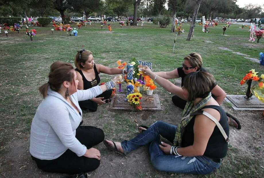 Family members Janie Briones (clockwise from top right), Matilda Briones, Cat Briones and their aunt Martha Cavazos make a toast to Briones' son, Michael James Briones, who had passed away three years ago on All Souls Day at San Fernando Cemetery No. 2 on Wednesday, Nov. 2, 2011.  Photo: Kin Man Hui, KIN MAN HUI/SAN ANTONIO EXPRESS-NEWS / San Antonio Express-News