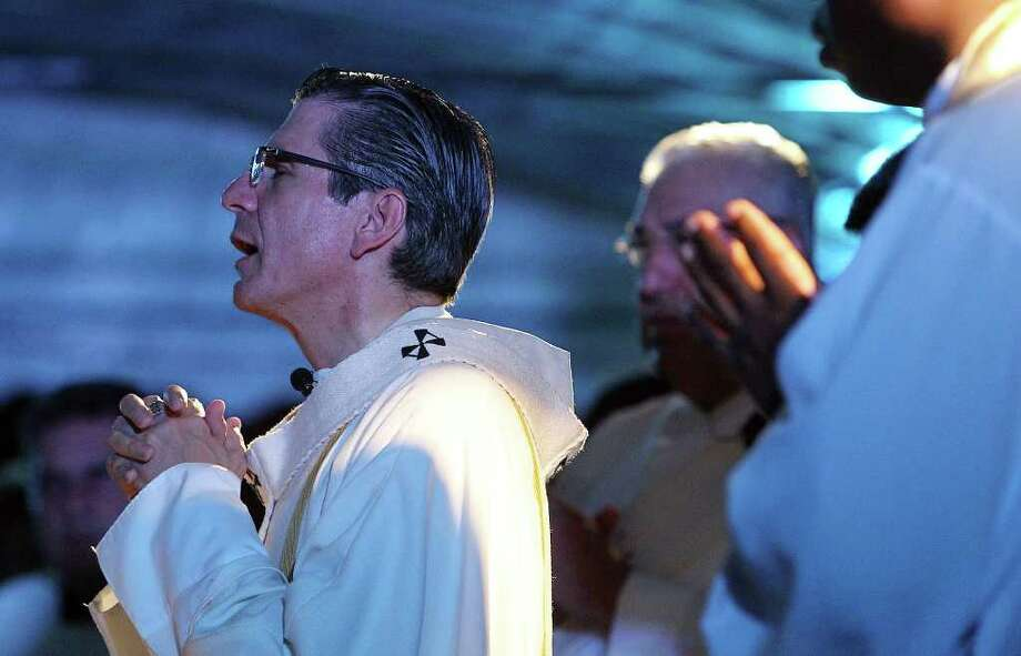 Archbishop Gustavo Garcia-Siller delivers an All Souls Day mass at San Fernando Cemetery No. 2 on Wednesday, Nov. 2, 2011. Family members of the departed also paid homage to their loved ones at the cemetery. Photo: Kin Man Hui, KIN MAN HUI/SAN ANTONIO EXPRESS-NEWS / San Antonio Express-News