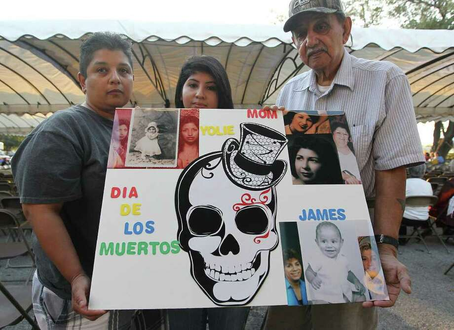 Cynthia Valdez (from left), Yolanda Romero and Emilio Valdez hold a sign that pays homage to family members who had passed away and laid to rest at San Fernando Cemetery No. 2 on Wednesday, Nov. 2, 2011.  Photo: Kin Man Hui, KIN MAN HUI/SAN ANTONIO EXPRESS-NEWS / San Antonio Express-News