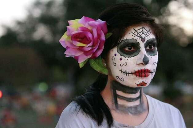 Cynthia Ramirez (center) stands with her face painted for All Souls Day as she listens to a mass given by Archbishop Gustavo Garcia-Siller at San Fernando Cemetery No. 2 on Wednesday, Nov. 2, 2011. Ramirez said the face painting was a Mexican tradition and she did it to pay respect to her grandparents who were laid to rest at the cemetery. Ramirez was joined by hundreds of other families who went and paid homage to their loved ones. Photo: Kin Man Hui, KIN MAN HUI/SAN ANTONIO EXPRESS-NEWS / San Antonio Express-News