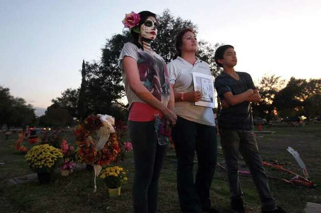 Cynthia Ramirez (center) stands with her face painted for All Souls Day with her aunt Esther Guajardo and Guajardo's son Titos as they listen to a mass given by Archbishop Gustavo Garcia-Siller at San Fernando Cemetery No. 2 on Wednesday, Nov. 2, 2011. Ramirez said the face painting was a Mexican tradition and she did it to pay respect to her grandparents who were laid to rest at the cemetery. Ramirez and Guajardo were joined by hundreds of other families who went and paid homage to their loved ones. Kin Man Hui/kmhui@express-news.net Photo: Kin Man Hui, SAN ANTONIO EXPRESS-NEWS / San Antonio Express-News