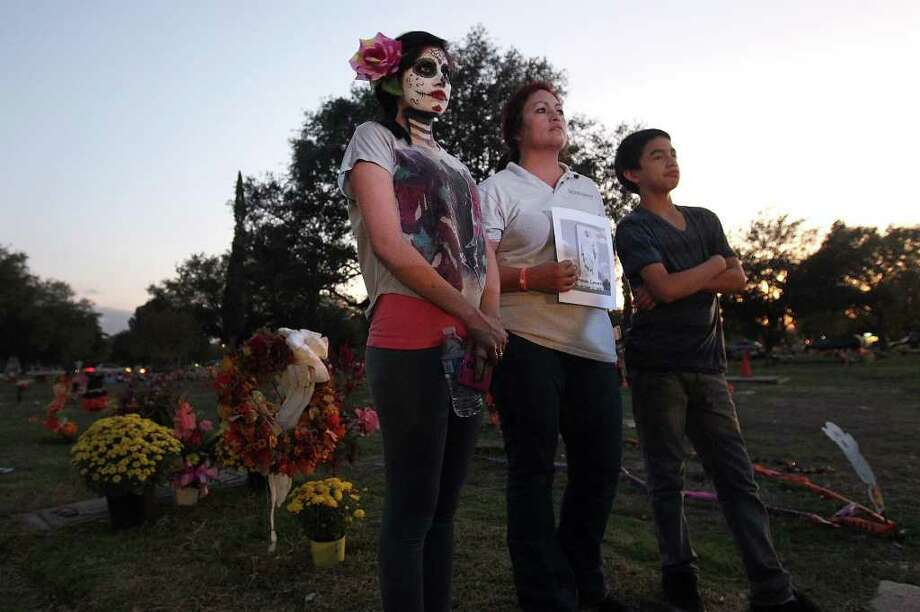 Cynthia Ramirez (center) stands with her face painted for All Souls Day with her aunt Esther Guajardo and Guajardo's son Titos as they listen to a mass given by Archbishop Gustavo Garcia-Siller at San Fernando Cemetery No. 2 on Wednesday, Nov. 2, 2011.  Photo: Kin Man Hui, SAN ANTONIO EXPRESS-NEWS / San Antonio Express-News