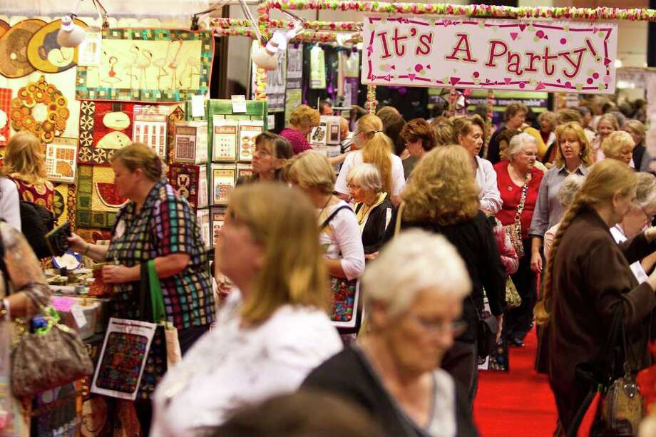 The International Quilt Festival's exhibitors hall is packed with shoppers looking to buy antiques, sewing supplies and jewelry on Wednesday in the George R. Brown Convention Center. Photo: Nick De La Torre / © 2011  Houston Chronicle