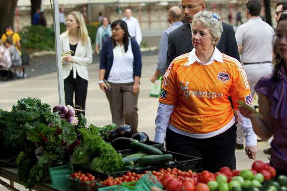 Mayor Annise Parker walks around the City Hall Farmers Market wearing a Houston Dynamo jersey Wednesday, Nov. 2, 2011, in Houston. The mayor urged Houstonians to cheer on the Dynamo in its MLS playoff match Thursday against the Philadelphia Union. Photo: Brett Coomer, Houston Chronicle / © 2011 Houston Chronicle