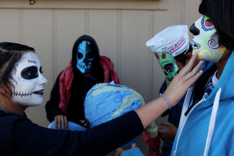 Theater Arts student Mariana Martinez, 13, touches the mask worn by Jose Bustos, 14, (right) as stud