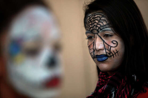 Theater Arts students Eve Younger, 13, (left) and Pamela Salazar, 13, wait for the  Dia de los Muertos parade to begin at Nimitz Middle School in San Antonio on Nov. 2, 2011. Photo: LISA KRANTZ / lkrantz@express-news.net
