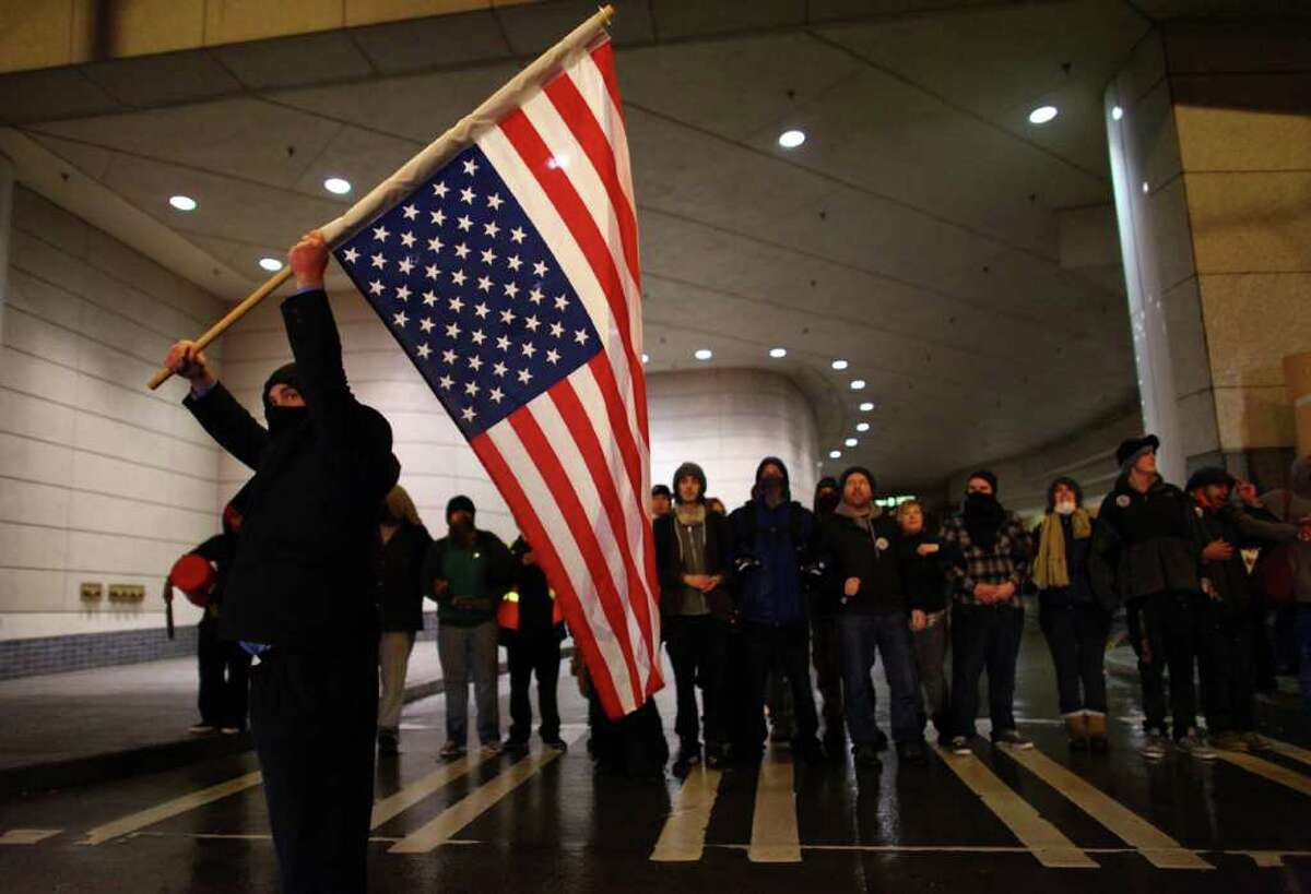 A protester holds a flag during an Occupy Seattle protest outside the Sheraton Hotel where Chase Bank CEO Jamie Dimon was speaking on Wednesday, November 2, 2011. A few hundred people tried to block the doors to the hotel during an event by the University of Washington business school.