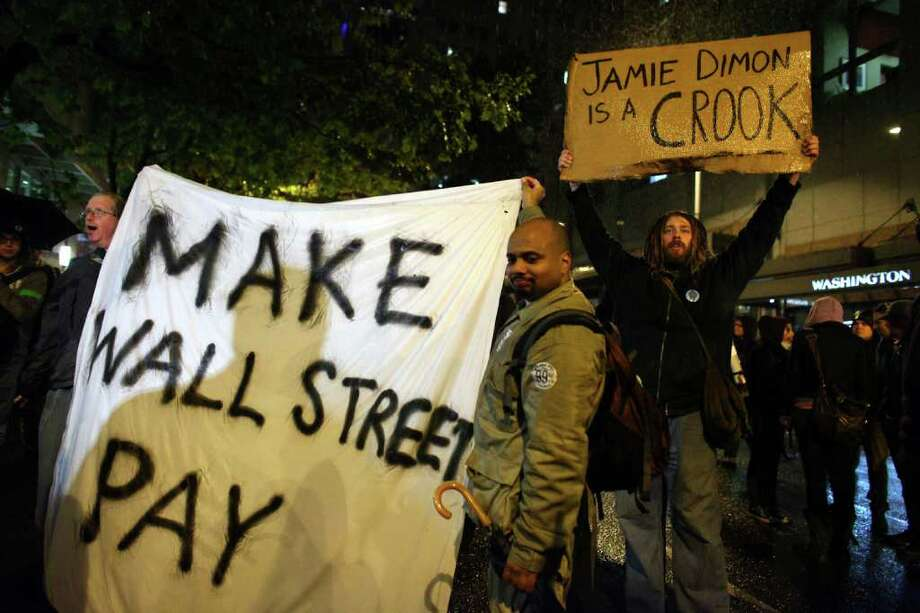 Protesters hold up signs during an Occupy Seattle protest outside the Sheraton Hotel where JPMorgan Chase CEO Jamie Dimon was speaking. Photo: JOSHUA TRUJILLO / SEATTLEPI.COM