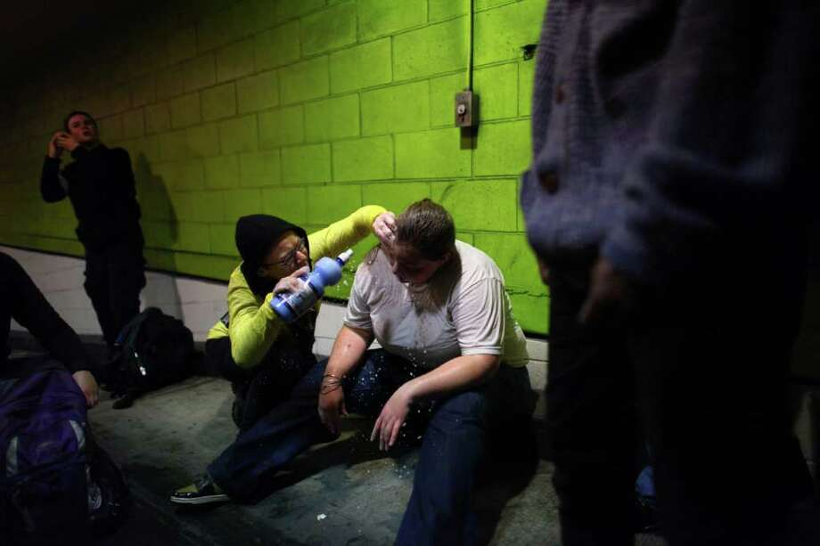 A protester hit with pepper spray is treated in a parking garage across from the Sheraton Hotel. Photo: JOSHUA TRUJILLO / SEATTLEPI.COM