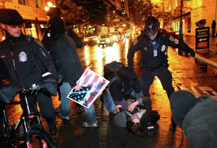 A protester is taken down by an undercover officer in front of the Sheraton Hotel after running from police. Photo: JOSHUA TRUJILLO / SEATTLEPI.COM