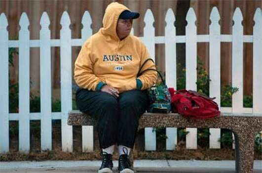 "Debra Stewart waits at the bus stop on Pecore Street  Thursday, Nov. 3, 2011, in Houston. ""It's cold, "" she said. ""I've got three  layers of clothes and thermal pants. I was planning on wearing shorts and a  t-shirt today."" (Cody Duty / Houston Chronicle)"