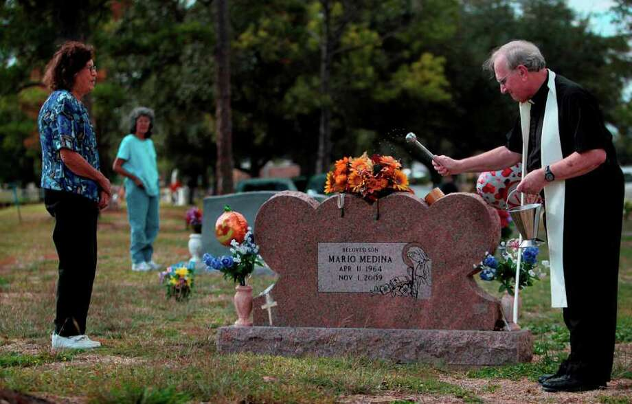 Toribia Medina, 78, stands by her son's grave as Rev. Reginald Nesvadba, 72, blesses the grave sites on All Souls Day at South Park Funeral Home and Cemetery on Tuesday, Nov. 1, 2011, in Pearland.  The blessing is a reminder that one day our bodies will be resurrected and rejoin our souls in heaven. Catholics believe that when a person dies only the soul goes to heaven. Photo: Mayra Beltran, Houston Chronicle / © 2011 Houston Chronicle