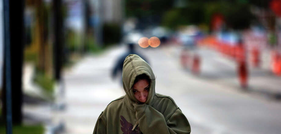 "Lynn Gonzalez, 32, keeps bundled up while walking home on  the 2800 block of Fulton St. as colder temperatures made their way into the  Houston area Thursday, Nov. 3, 2011, in Houston. ""It's cold I'm not use to  it, I don't like it, "" Gonzalez said about the weather. (Johnny Hanson / Houston Chronicle) / © 2011 Houston Chronicle"